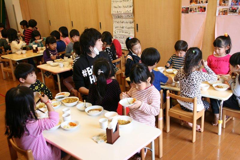 異年齢の子どもたちが一緒に食事を楽しんでいる