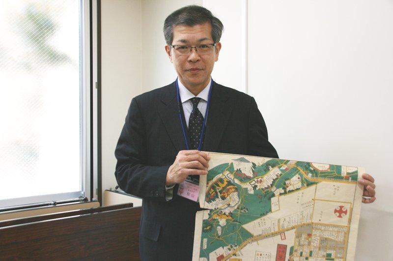 「染井・王子・巣鴨辺絵図」を持つ学芸員 秋山さん