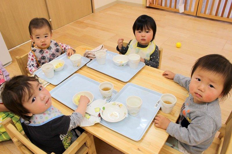 午後のおやつを楽しむ乳児クラスの園児