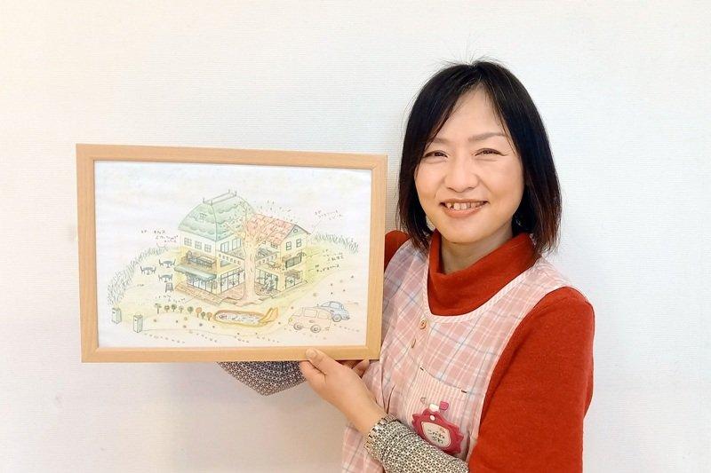 理想の「保育サポーター はちっ子」を描いた絵を手にする小金沢さん