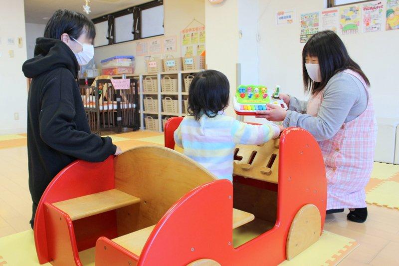 遊具で遊ぶ子どもを見守るママと、ひろばのスタッフ